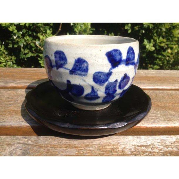 Glaseret tekop med underkop med blå blomst
